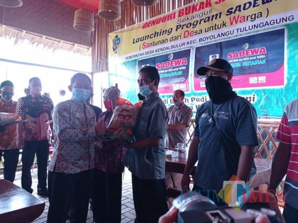 Kepala Desa Kendalbulur Anang Mustofa saat menyerahkan bibit padi program Sadewa