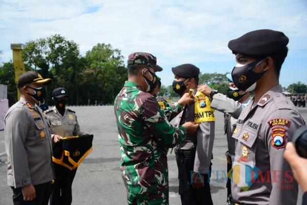 Dandim 0818 Letkol Yusub Dody saat menyematkan tanda pengamanan TPS pada anggota (Hendra Saputra)