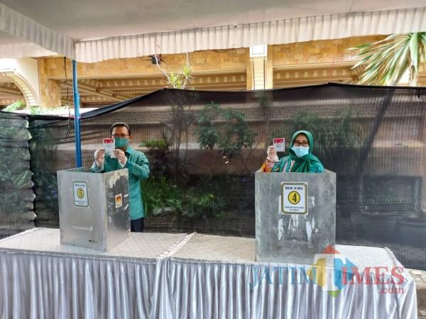 Gus Ali Ahmad bersama istri saat menggunakan hak suaranya di TPS 02, Desa Donowarih, Kecamatan Karangploso, Kabupaten Malang, Rabu (9/12/2020). (Foto: Tubagus Achmad/MalangTimes)