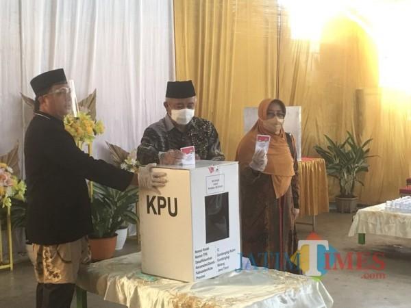 Bupati Malang Sanusi (tengah) beserta istri ketika memasukkan surat suara ke kotak yang telah disediakan oleh KPU (Foto : Ashaq Lupito / MalangTIMES)