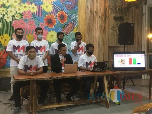 Ketua Umum Milenial Utas Zulham Akhmad Mubarrok (tengah, jas hitam) saat membacakan hasil real count versi Tim Milenial Utas. (Foto : Ashaq Lupito / MalangTIMES)
