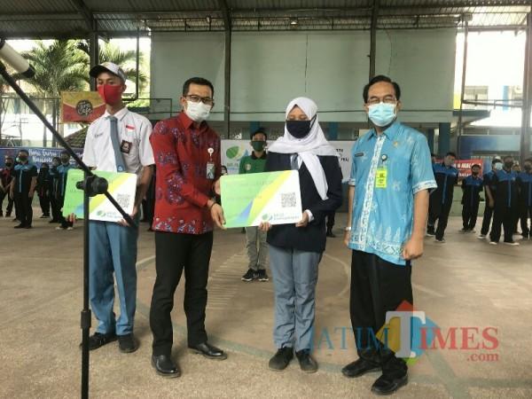 Kepala BPJS Ketenagakerjaan Cabang Malang Raya Imam Santoso (batik merah), Kepala SMKN 6 Malang Sidik Priyono (batik biru). (Foto: Ima/MalangTIMES)