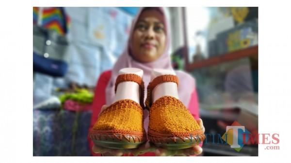Retna Widiyawati ketika menunjukkan produk sepatu berbahan benang rajut. (Foto: Bams Setioko/JatimTIMES)