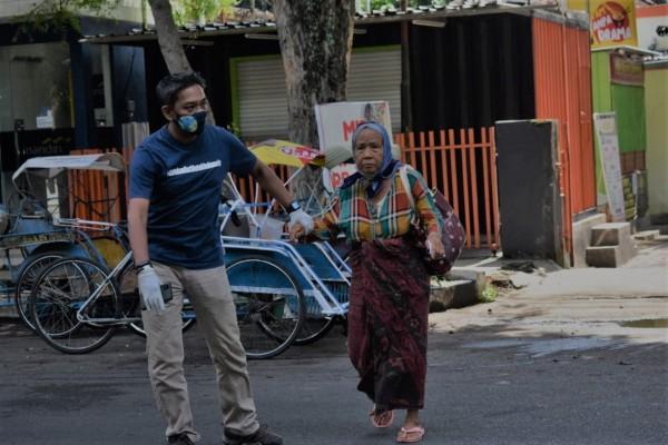 Baskoro, Founder Climate Change Frontier (CCF) saat membantu seorang nenek menyeberang jalan (foto :Istimewa)