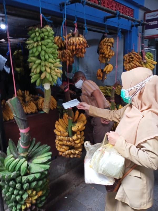 Petugas kesehatan dari Puskesmas Rampal Celaket saat membagikan masker di area Pasar Klojen. (Foto: Dokumentasi Puskesmas Rampal Celaket).
