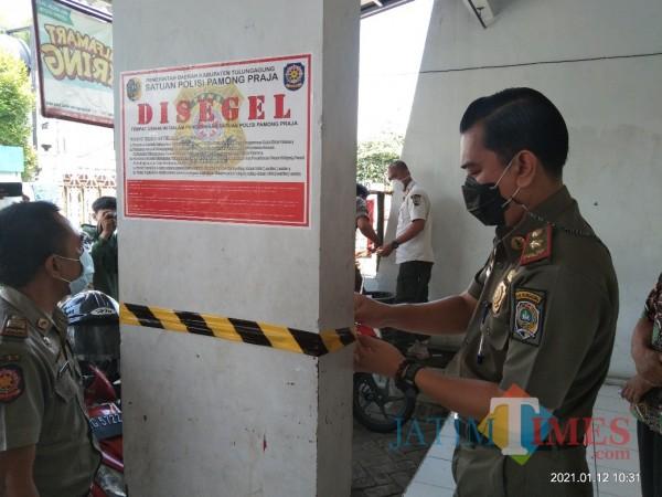 Satpol PP Tulungagung saat memasang segel dan pita di toko modern di Jalan Semeru Tulungagung (Joko Pramono for Jatim TIMES)