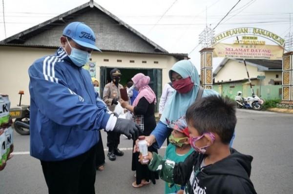 Wali Kota Madiun Maidi saat membagikan susu kepada masyarakat di Kelurahan Banjarejo.