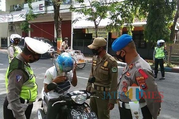 Petugas gabungan saat memberhentikan warga yang tidak memakai masker (Foto:Istimewa/JatimTIMES.com)