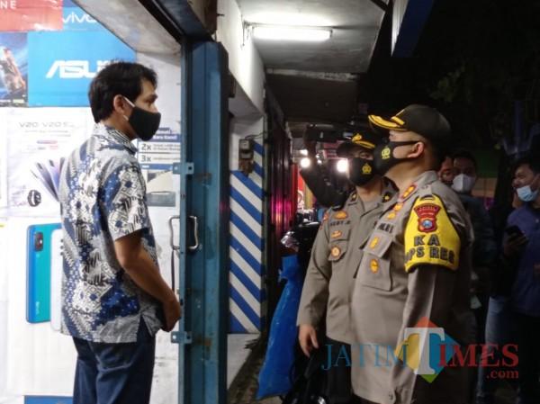 Kapolres Malang, AKBP Hendri Umar saat menegur salah satu toko handphone di Kepanjen yang masih buka di jam malam (Hendra Saputra)