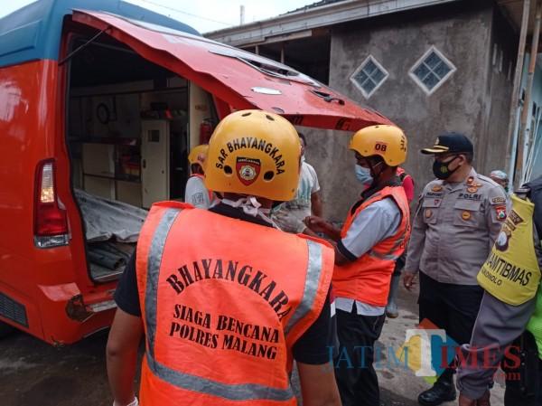 Kapolsek Bululawang, Kompol Pujiyono (tengah bertopi) saat mengevakuasi mayat terhanyut di sungai Senin (11/1/2021) (Hendra Saputra)