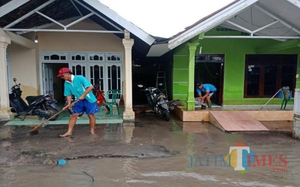 Sejumlah warga Dusun Beluk, Desa Jombok, Kecamatan Kesamben tampak mulai membersihkan rumah dari sisa banjir. (Foto : Adi Rosul / JombangTIMES)
