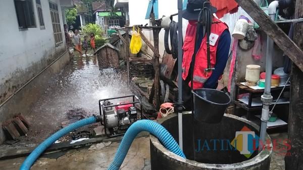Relawan PMI Kabupaten Jember saat melakukan pengurasan sumur warga yang kotor akibat banjir beberapa waktu yang lalu (foto : istimewa / Jatim TIMES)
