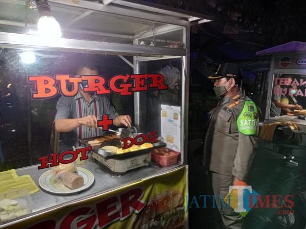 Anggota satpol PP saat memberikan teguran kepada salah satu penjual burger di Kepanjen. (Hendra Saputra)