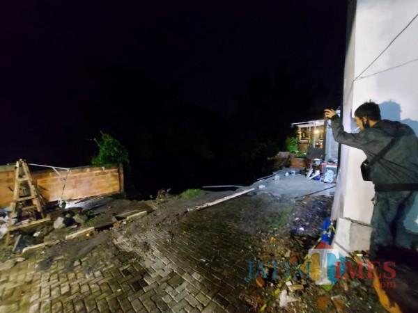 Kondisi depan rumah milik korban atas nama Roland Sumarno (40) yang ambles dan terbawa arus deras Sungai Bangau, Senin (18/1/2021). (Foto: Tubagus Achmad/MalangTimes)