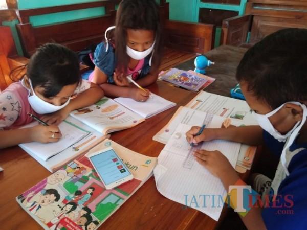 Sejumlah anak terlihat belajar dengan menggunakan satu HP untuk digunakan bersama-sama saat jam belajar daring dimulai. (Foto : Adi Rosul / JatimTIMES)