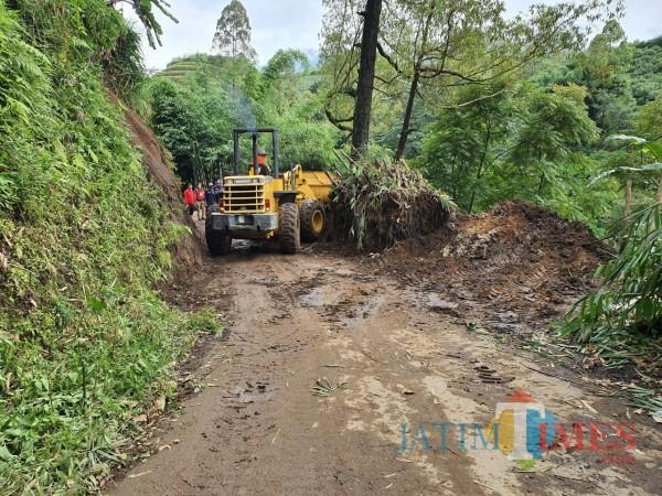 Alat berat saat mengangkut material tanah longsor di Desa Tulungrejo, Kecamatan Bumiaji.