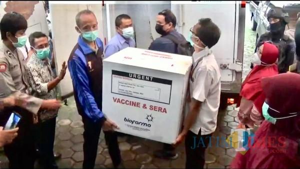 Petugas saat menurunkan vaksin Covid-19 Sinovac dari mobil di Puskesmas Batu, Senin (25/1/2021). (Foto: Irsya Richa/MalangTIMES)