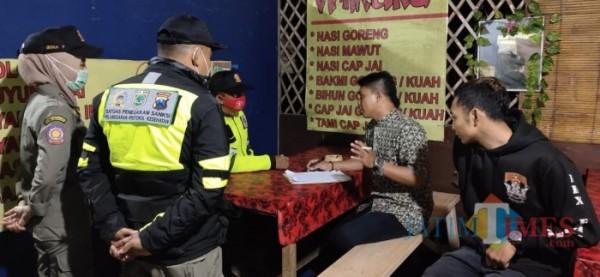 Petugas gabungan yang melakukan operasi yustisi di salah satu warung di Kota Batu beberapa saat lalu. (Foto: Irsya Richa/MalangTIMES)