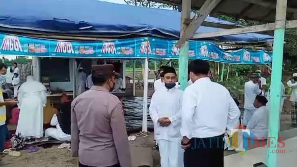 Polisi saat mendatangi padepokan tempat ritual yang ada di samping makam di area persawahan Desa Pancakarya ,Ajung, Jember. (foto : istimewa / Jatim TIMES)