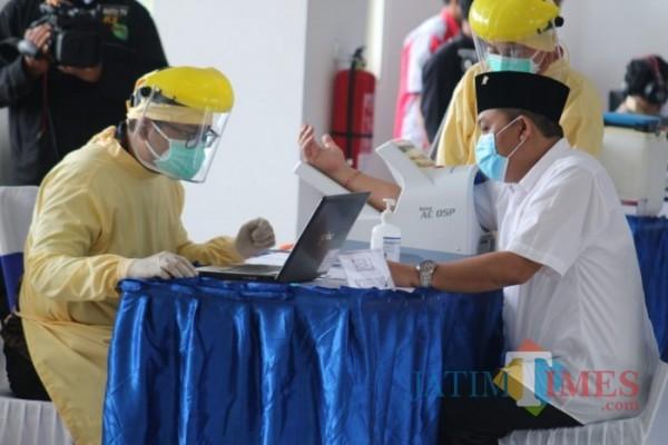 Petugas kesehatan (ber-APD) saat melakukan skrining sebelum vaksinasi kepada Ketua DPRD Kota Malang I Made Riandiana Kartika. (Foto: Ahmad Amin/MalangTIMES).