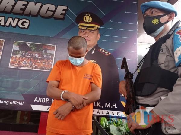 Tersangka sodomi (baju orange) terus menunduk saat di rilis oleh Polres Malang, Kamis (28/1/2021) (Hendra Saputra/MalangTIMES)