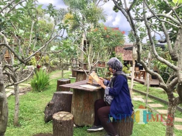 Pengunjung sedang memilih menu di tengah kebun apel D'Goendoe. (Foto: Irsya Richa/MalangTIMES)