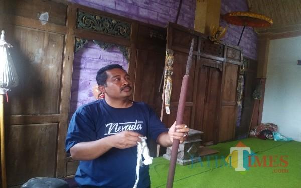 Parlan Kepala Desa Tugu Kecamatan Sendang Kabupaten Tulungagung dan tombak yang didapat dari Punden Sembojo / Foto : Anang Basso / Tulungagung TIMES