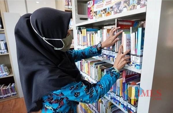 Salah satu pengunjung sedang memilih buku di perpustakaan Balai Kota Among Tani Kota Batu. (Foto: Irsya Richa/BatuTIMES)