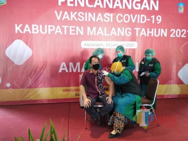 Kadinkes Kabupaten Malang Arbani Mukti Wibowo (pakai batik) saat melaksanakan pencanangan vaksinasi covid-19, Sabtu (30/1/2021). (Foto: Ashaq Lupito/JatimTIMES)