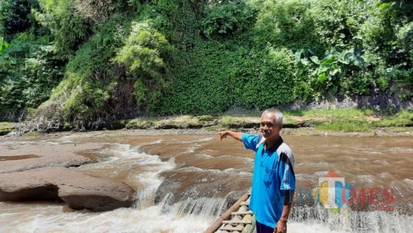 Suhamim saat menunjukkan lokasi penemuan mayat perempuan tanpa identitas di perairan Sungai Brantas, Minggu (7/2/2021). (Foto: Tubagus Achmad/ MalangTIMES)