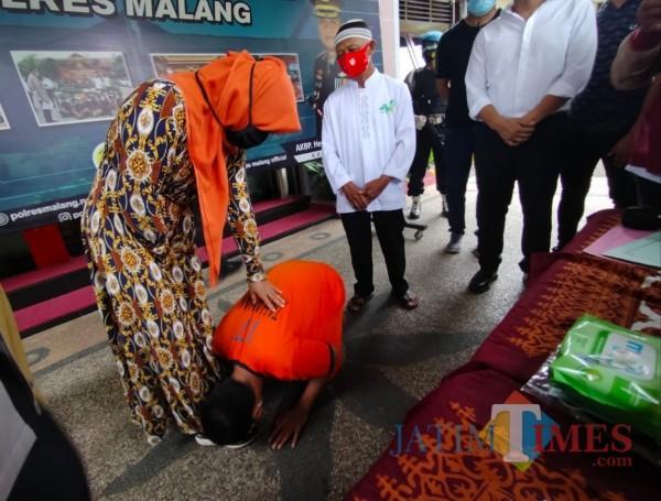 Qoim Lidinillah (baju orange) bersimpuh cium kaki ibu kandungnya usai dilepaskan Polres Malang, Senin (8/2/2021) (Hendra Saputra/MalangTIMES)