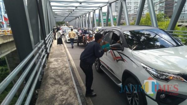Salah satu aksi penggalangan dana di kawasan pertigaan Jalan Soekarno-Hatta (Suhat) Kota Malang, Selasa (2/2/2021). (Foto: Tubagus Achmad/MalangTIMES)