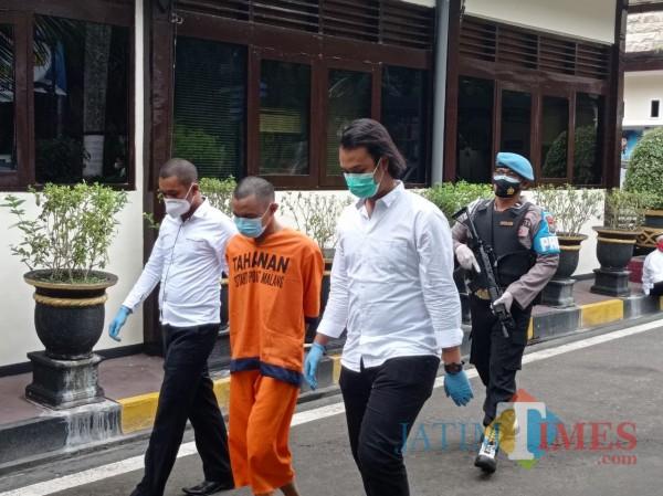 Tersangka MHS (baju orange) saat digelandang Polisi di Mapolres Malang (Hendra Saputra)