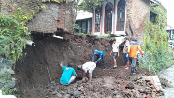 Personel BPBD Kabupaten Malang bersama Muspika setempat dan warga saat membersihkan material longsoran (foto: BPBD Kabupaten Malang for MalangTIMES)