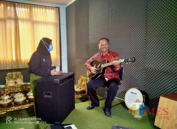 Prof Dr Abdul Haris MAg, Rektor UIN MALIKI Malang, saat berada di ruang seni Fakultas Humaniora, tengah memainkan alat musik gitar (Anggara Sudiongko/MalangTIMES)