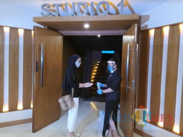 Salah satu penerapan protokol kesehatan kepada pengunjung saat akan memasuki studio di salah satu bioskop di Kota Malang. (Foto: Istimewa)