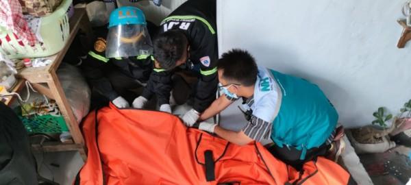 Petugas saat melakukan evakuasi terhadap jenazah korban di kamar mandi rumahnya, Selasa (16/2/2021). (Foto: Satkom RJT Kota Malang)