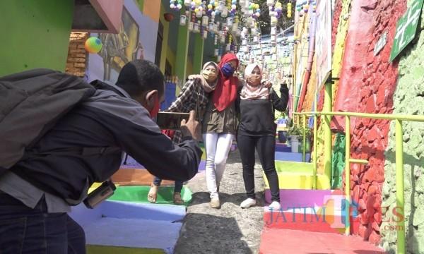 Wisatawan saat berswa foto di area Kampung Warna-Warni Jodipan Kota Malang. (Ahmad Amin/MalangTIMES).