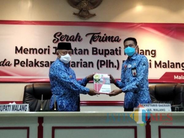 Bupati Malang terpilih, Sanusi (kiri) saat menyerahkan memori jabatan Plh Bupati Malang kepada Wahyu Hidayat (kanan), Rabu (17/2/2021). (Foto: Ashaq Lupito/JatimTIMES)