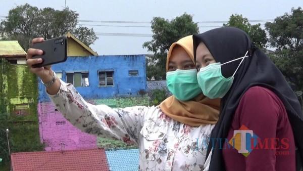 Dua orang pengunjung yang tengah asyik selfie di kawasan Kampung Tridi, Kota Malang. (Foto: Dokumentasi MalangTIMES)