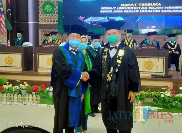 Rektor UIN Maliki Malang Prof Dr Abdul Haris (kanan) usia mengukuhkan dekan Fakultas Ekonomi sebagai guru besar. (Anggara Sudiongko/MalangTIMES)