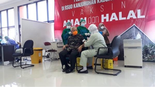 Bupati Malang terpilih Sanusi (masker oranye) saat menjalani suntikan pertama vaksinasi di RSUD Kanjuruhan, (18/2/2021). (Foto: istimewa)