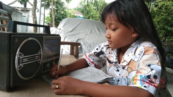 Sambil dengar radio, seorang siswa mengerjaka tugas dari sekolah (Joko Pramono for Jarim TIMES)