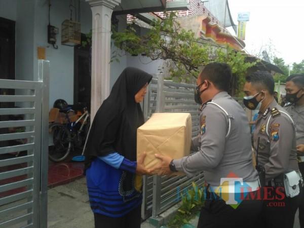 AKP I Putu Angga menyerahkan bantuan kepada warga. (Foto: Bramastyo Dhieka Anugerah / Jatim Times)