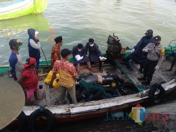 Proses evakuasi mayat Mr. X oleh petugas kepolisian yang dibantu nelayan (Foto: Ist/JatimTIMES)