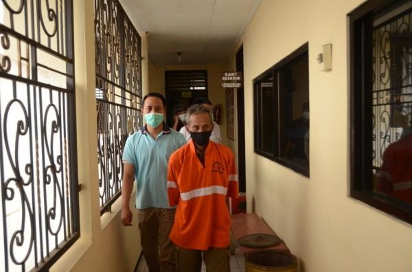 Slamet Hadianto (baju orange) ketika digelandang oleh anggota Unit Reskrim Polsek Klojen. (Foto: Polsek Klojen)