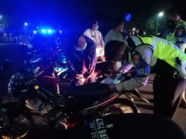 Petugas Polresta Malang Kota saat melakukan penindakan terhadap pengendara bermotor, Minggu (21/2/2021) malam. (Foto: Humas Polresta Malang Kota)