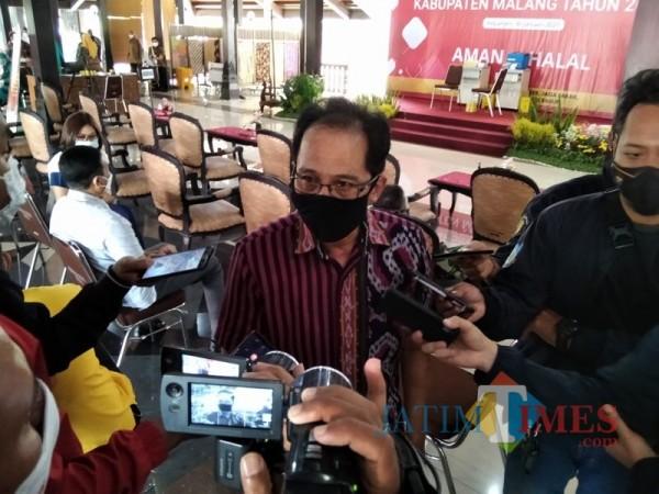 Kadinkes Kabupaten Malang Arbani Mukti Wibowo (pakai kaca mata) saat menjelaskan evaluasi kasus aktif Covid-19 selama PPKM mikro. (Foto: Dokumen JatimTIMES)