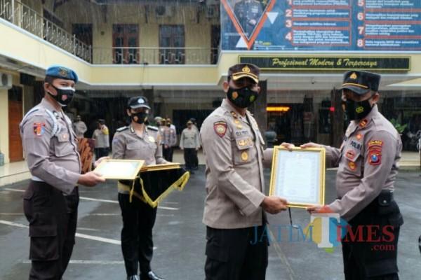 Kapolsek Pasirian Iptu Agus Sugiharto SH, MH ketika menerima penghargaan dari Kapolres Lumajang (Foto : Moch. R. Abdul Fatah / Jatim TIMES)