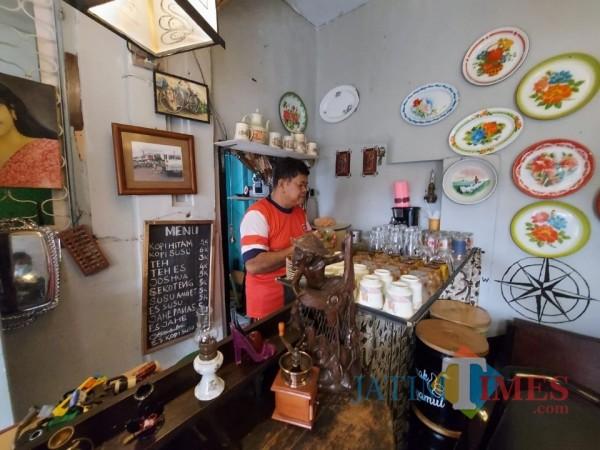 Pengelola warung Hamur Kopi Mbah Ndut Rudi Haris saat membersihkan cangkir-cangkir kopi, Minggu (21/2/2021). (Foto: Tubagus Achmad/MalangTIMES)